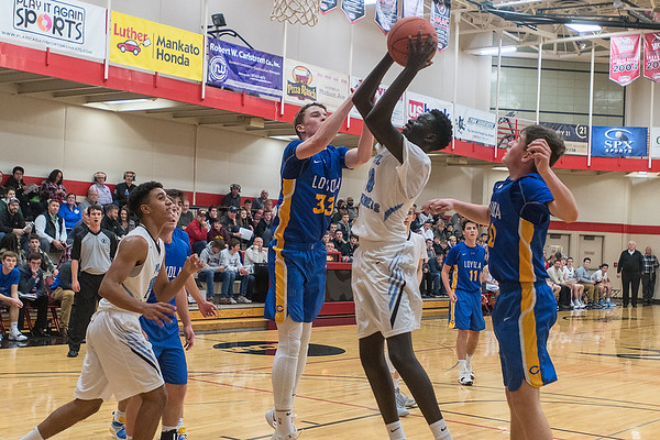 Minnesota Valley Lutheran's Dunwa Omot grabs an offensive rebound and puts it up past Mankato Loyola's Brendan Kane (33) and Ben Ellingworth (right) in the first half of Thursday first round game of the Kwik Trip Holiday Tournament. Photo by Jackson Forderer
