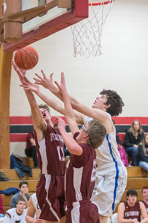 Lake Crystal-Wellcome Memorial's Caleb Shelton (right) fights for a rebound against Fairmont's Zach Jorgensen (left) and Joey Flohrs in the first half of Thursday's game at the Kwik Trip Holiday Tournament. LCWM lost to the Cardinals 51-27. Photo by Jackson Forderer