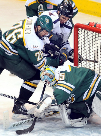 The University of Alaska Anchorage's Tyler Currier (26) tries to keep Minnesota State's Brett Knowles from the puck as goalieChris Kamal tries to cover it up during the first period Friday at the Verizon Wireless Center.