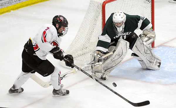 Mankato West's Derek Frentz tries to shoot the puck around Faribault goalie Cody Morsching during the second period Thursday at All Seasons Arena.