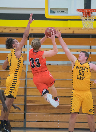 Mankato East's Jordan Merest (50) and Damani Hayes contest a shot put up by Winona's Jake Reeck in the first half of Friday's Big 9 conference game played at East. Photo by Jackson Forderer