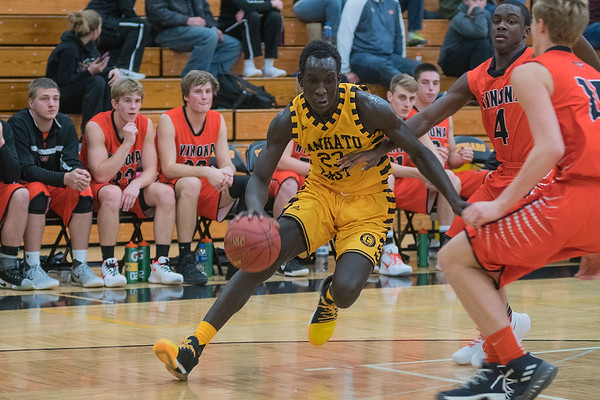 Mankato East's Uhana Ochan drives to the basket while being defended by Winona's Terrell Hall (4) and Bradley Winter in the first half of Friday's Big 9 conference game. Photo by Jackson Forderer