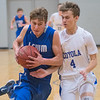 Lake Crystal Wellcome Memorial's Garret Wiens (left) drives to the basket and gets fouled by Mankato Loyola's Matthew Helget during the first half of Tuesday's game. Photo by Jackson Forderer