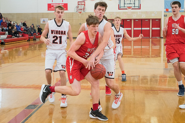 Mankato West's Dawson Frericks has the ball stripped by Winona's Brody Bittle in the second half of Saturday's game. Frericks recovered the ball on the play and was fouled by Bittle. West defeated Winona 80-71 in a Big 9 conference matchup. Photo by Jackson Forderer
