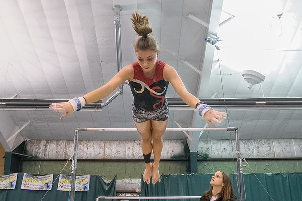 Mankato West's Taryn Sellner dismounts from the uneven bars as head coach Samantha Gertner looks on during practice at K&G Gymnastics on Thursday. This will be Sellner's third year on varsity as a sophomore. Photo by Jackson Forderer