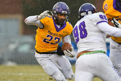 Minnesota State's Nate Gunn (left) cuts back to avoid Tarleton State's Sean Walton (98) in last Saturday's playoff game. Gunn broke the school record for most carries in a single game in the Mavericks 13-10 win. Photo by Jackson Forderer