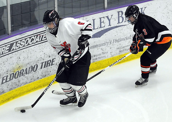 Mankato West's Justine Scheller keeps the puck away from Winona's Kaylin Wagner during the first period Saturday at All Seasons Arena.