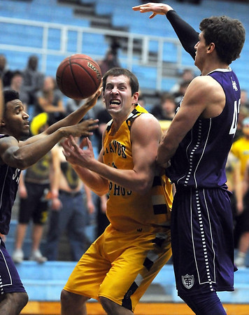 Gustavus Adolphus College's Reed Sallstrom has the ball knocked out of his hands as he drives between a pair of St. Thomas defenders during the first half Wednesday in St. Peter.