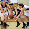 Mankato Loyola's Rae Ann Dose is surrounded by United South Central's Taylor Steckelberg (left) and Eryn Eilertson as she scoops up a loose ball during the first half Saturday at the Fitzgerald gym.
