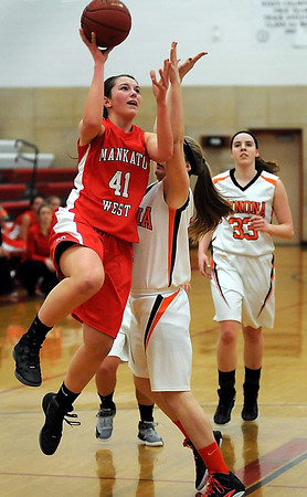 John Cross<br /> Mankato West's Cara Christiansen drives by Winona defender Greer Kosidowski for a lay-up during first period action Friday.