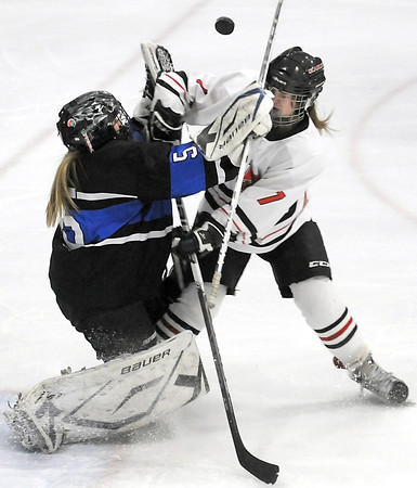 Pat Christman<br /> Mankato West's Courtney Bloemke collides with St. Peter/Le Sueur-Henderson/Tri City United goalie Veronica Sinell as the puck floats between them during the first period Thursday at All Seasons Arena.