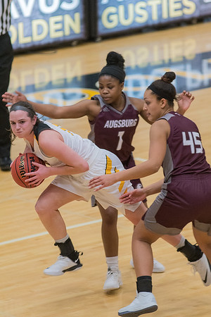 Gustavus' escapes from a trap by Augsburg's Arianna Jones (1) and Jazmy Solseth (45) as the Gusties tried to mount a comeback in the fourth quarter. Photo by Jackson Forderer