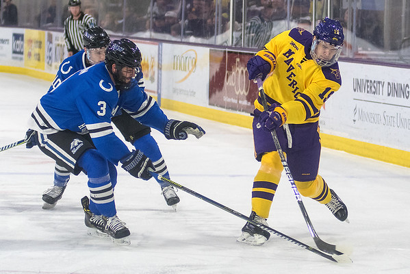 Minnesota State's Chris Van Os-Shaw takes a shot on goal while being defended by University of Alabama-Huntsville's Drew Lennon in the first period of Friday's game. Van Os-Shaw scored his first goal for the Mavericks in their 6-1 victory. Photo by Jackson Forderer