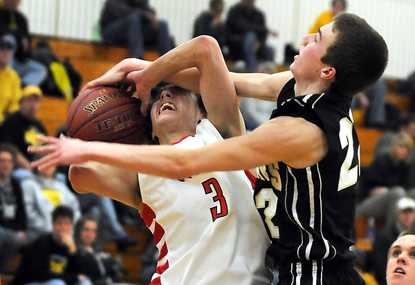 Mankato East's Nic Seiler fouls Mankato West's Tyler Stoffel during the first half Tuesday at the East gym.