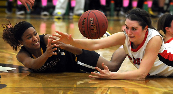 Mankato East's Minnie Frederick (left) and Mankato West's Cara Christiansen reach for a loose ball during the first half Tuesday at the East gym.