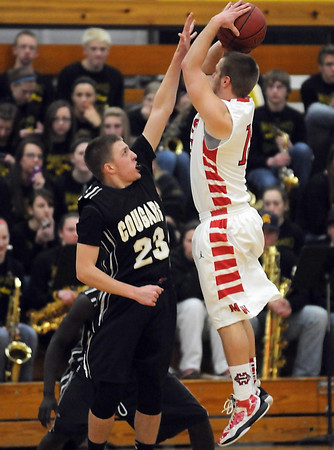 Mankato West's Alex Knutson shoots over Mankato East's Jordan Grams during the first half Tuesday at the East gym.
