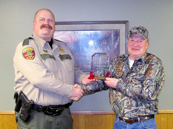 Submitted photo<br /> Minnesota Department of Natural Resources Conservation Officer Chris Howe presents longtime Firearms Safety and Advanced Hunter Education instructor Rick Meuer with a plaque recognizing his 40 years as a volunteer instructor.