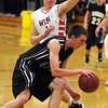 Mankato East's Matt Bornholdt drives around Mankato West's Jake Dale during the first half Tuesday at the East gym.