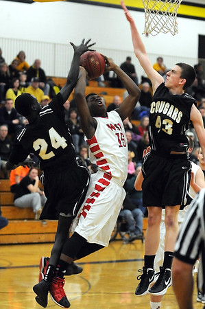 Mankato West's Travon Jones splits the defense of Mankato East's Gorg Alhad (24) and Matt Bornholdt (43) during the first half Tuesday at the East gym.
