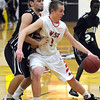Mankato East's Brandon Adema defends Mankato West's Jake Dale during the first half Tuesday at the East gym.