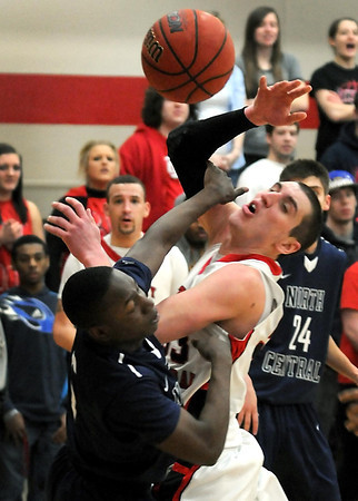Bethany Lutheran College's Gavin Kroehler has the ball knocked out of his hand by North Central's Chauncee Holligsworth during the first half of their UMAC tournament game Wednesday.