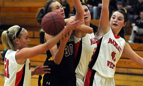 Mankato East's Taylor Karge (30) is surrounded by Mankato West's Malorie Veroeven (21), Lauren Resner (55) and Cara Christiansen (41) as the ball is knocked from her hands during the first half Tuesday at the East gym.
