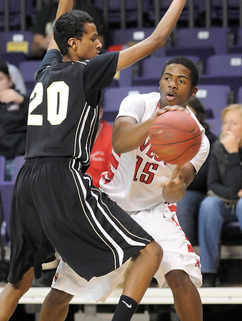 Pat Christman<br /> Mankato West's Travon Jones passes around East's Hussein Mohamoud during the first half Tuesday at Bresnan Arena.