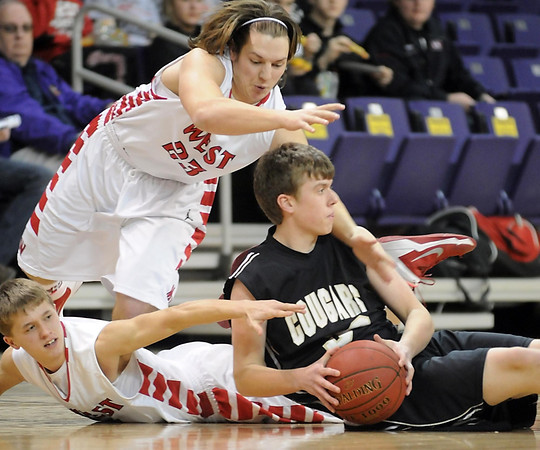 Pat Christman<br /> Mankato East's Sam Ahrens (33) looks to pass after recovering a loose ball from Mankato West's Jake Makela (2) and Ryan Schlichte (23) during the first half Tuesday at Bresnan Arena.