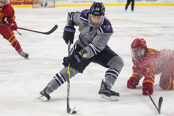 Minnesota State's Dallas Gerads (22) drives the net after passing by a defensive slide from Ferris State's Ryker Killins in the second period of Saturday's game played at the Verizon Center. The Mavericks are in first place of the WCHA after sweeping Ferris State. Photo by Jackson Forderer