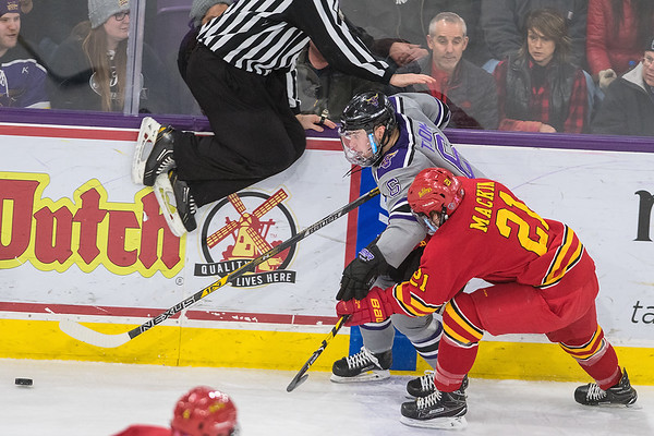Parker Tuomie of Minnesota State chases after the puck against Ferris State's Corey Mackin as a referee jumps out of the way of action in the second period of Saturday's game played at the Verizon Center. The Mavericks swept Ferris Sate with a 4-2 victory. Photo by Jackson Forderer