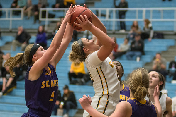 St. Catherine's Ashley Fosness (left) tries to block a shot put up by Gustavus' Justine Lee in the second half of Tuesday's game played in St. Peter. The Gusties dominated the game and won 65-38. Photo by Jackson Forderer