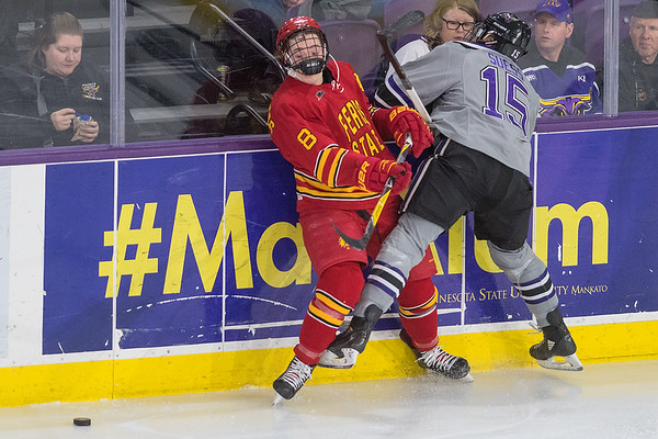 Minnesota State's C.J. Suess nearly takes the helmet off of Ferris State's Andrew Dorantes while checking him into the boards during Friday's game played at the Verizon Center. Photo by Jackson Forderer