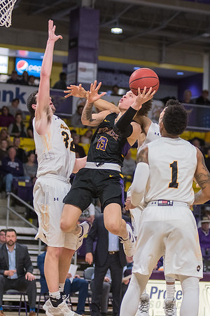 Tre Baumgardner of Minnesota State hangs in the air while taking a shot and being defended by Wayne State's Jordan Janssen in the second half of Saturday's NSIC matchup. MSU held their lead and won 89-78. Photo by Jackson Forderer