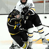Gustavus Adolphus College's Corey Leivermann knocks St. Olaf's Kevin Harris off of the puck during the first period Friday at Don Roberts Ice Rink.