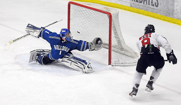 Pat Christman<br /> Mankato West's Zachary Erickson puts the puck over the outstretched glove of Le Sueur-Henderson/St. Peter's Zeke Haugen for a goal in the first period of their Section 1A tournament game Friday at All Seasons Arena.