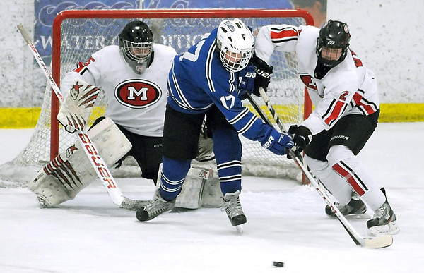 Pat Christman<br /> Le Sueur-Henderson/St. Peter's Mac Malecha (17) and Mankato West's Scott McKissing battle for the puck in front of West goalie Conor Wollenzien during the first period Friday at All Seasons Arena.