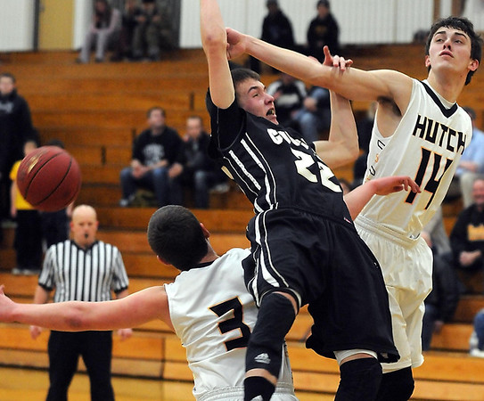 Pat Christman<br /> Mankato East's Nic Seiler (22) falls over the back of Hutchinson's Mason Kucera (3) while battling for a rebound with Jayden Juergensen (14) during the first half Tuesday at the East gym.