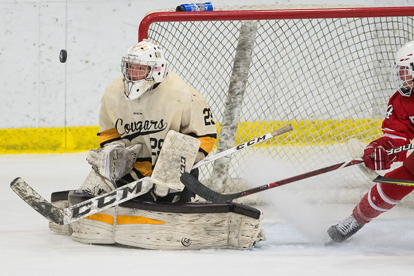 Mankato East goalie Jack Cusey keeps his eyes on the puck as Austin's Bryar Flanders (right) tries to track down a rebound in the second period of Thursday's Section 1A playoff game played at All Seasons Arena. Cusey held the Packers scoreless to help the Cougars win 2-0. Photo by Jackson Forderer