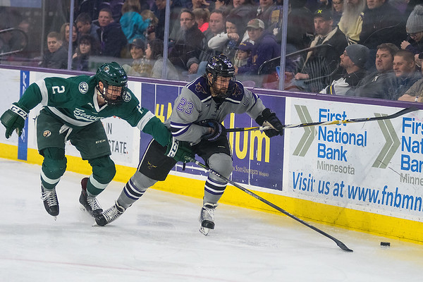 Minnesota State's Nicholas Rivera (23) chases down the puck along the boards against Bemidji State's Dan Billett (2) in the third period of Saturday's game. The Mavericks took five out of a possible six points in their series against the Beavers. Photo by Jackson Forderer