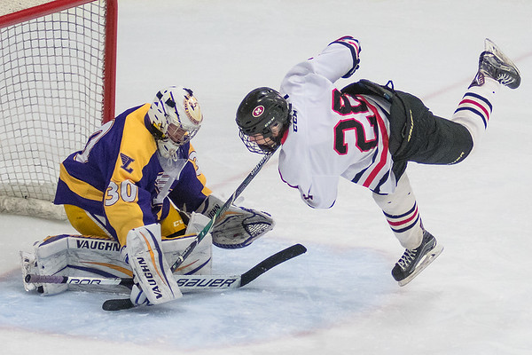Mankato West's Ethan Swenson (28) drives to the net during a break away chance on Rochester Lourdes' goalie Ryan Smith in a Section 1A playoff game played on Thursday at All Seasons Arena. Smith made the save and helped his team to a 2-1 win over the Scarlets. Photo by Jackson Forderer