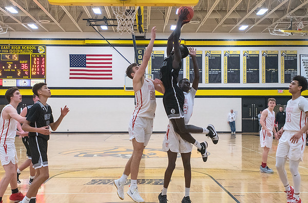 Joich Gong of Mankato East tries for a soaring dunk against Mankato West's Spencer Spaude and Buomkuoth Jock in the second half. Gong missed the dunk but the Cougars got the last laugh in winning Saturday's game and sweeping the Scarlets this season. Photo by Jackson Forderer