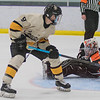 Hayden Guillemette of Mankato East/Loyola watches his shot slip underneath the outstretched glove of Winona's goalie Alex Benson in the second period as the Cougars pulled away from the Winhawks. The Cougars won the Section 1A playoff game 8-0. Photo by Jackson Forderer