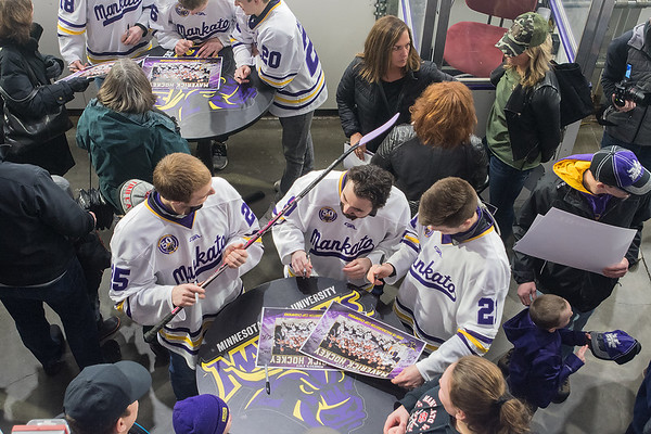 Charlie Gerard (center) ducks to avoid getting hit by a fan's hockey stick held by Riese Zmolek (left) as Zmolek looked for a place to put his signature during an autograph session at the Verizon Center on Tuesday. Photo by Jackson Forderer