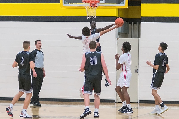 Mankato East's Joich Gong blocks a reverse layup attempt from Mehki Collins of Mankato West in the second half of Saturday's game. The Cougars won with a defense that smothered the Scarlet offense. Photo by Jackson Forderer