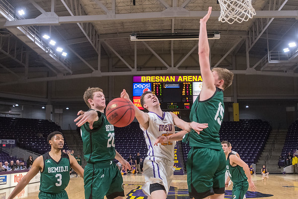 Minnesota State's Karson Arrenholz loses control of the ball while driving the basket against Bemidji State's Cody Landwehr (right) and Logan Longo in the second half of Wednesday's first round NSIC tournament game. Photo by Jackson Forderer