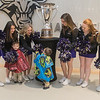Tucker Urevig (left), 4, and Kayden Urevig (center),  2, get horseplay with Minnesota State cheerleaders before they all got their picture taken in front of the MacNaughton trophy in the lobby of the Verizon Center on Tuesday. Photo by Jackson Forderer