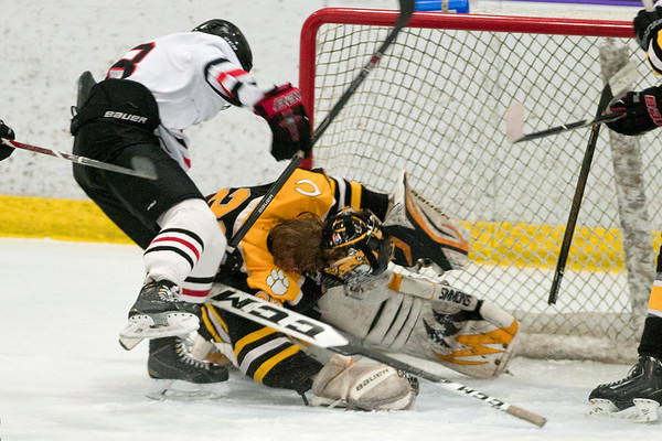 Mankato East goalie Jack Cusey has his helmet knocked off in a collision in front of the goal with Mankato West's Drew Steiert (8) in the second period. The second period ended with multiple penalties, with the third period starting with a 4-on-3. Photo by Jackson Forderer