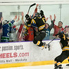Nick Salze of Mankato East jumps into the glass where the East students were congregated for the boys hockey game against Mankato West. Salze's goal in the third period helped seal the 5-2 win for the Cougars. Photo by Jackson Forderer