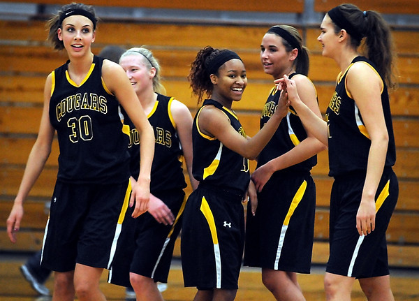 Mankato East's Minnie Frederick (center) is congratulated by her teammates after scoring her 1,000th career point Tuesday against Rochester Mayo at the East gym.