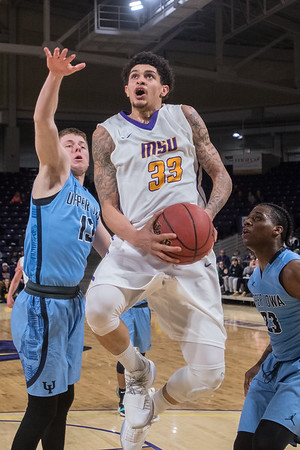 Minnesota State's Chris Hendrix (33) jumps past Upper Iowa's Quentin Blaue(left) and Dennis Austin III (right) on his way to a reverse layup in the second half in Friday's game. played at Bresnan Arena. Photo by Jackson Forderer